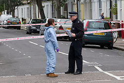 © Licensed to London News Pictures. 19/09/2013. London, UK. A forensic officer talks to a policeman at the cordon surrounding the site of a shooting on Coppock Close in Battersea London today (19/09/2013). Taking place at around 8pm last night a 19 year old male was pronounced dead at around 9pm. Photo credit: Matt Cetti-Roberts/LNP