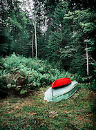 A red kayak atop a rowboat at a camp in Phippsburg, Maine.