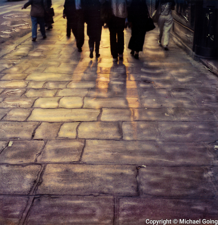 hand altered Polaroid SX-70 photo of group of pedestrians from the chest and waist down walking on the cobblestone sidewalk of Rue Rivoli in Paris France. Backlight with light shinning through their legs onto the cobblestone sidewalk
