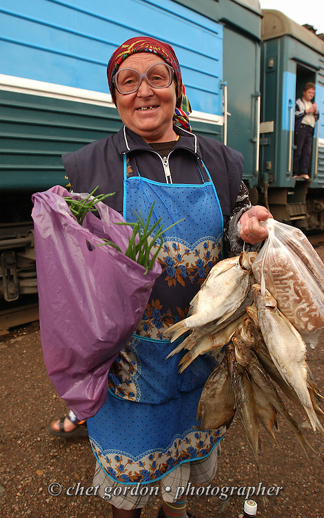 "A ""Babushka"" sells roasted fish along with roasted caviar during a stop along the Trans-Siberian Railway route for a locomotive change at Bolezeno Station in Bolezno, Siberia, Russian Federation on June 10, 2005."