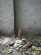 A wooden statuette of the Madonna and Child stands among dead leaves in an abandoned lot in the Hell's Kitchen neighborhood of Manhattan, New York City.