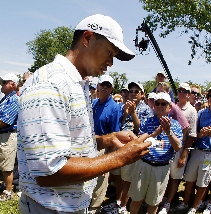 Tiger Woods of the US completes his scorecard as he walks off the ninth hole (his eighteenth hole of the day) following his round on the second day of the US Open Golf Championship at Winged Foot Golf Club in Mamaroneck, New York Friday, 16 June 2006.  Woods finished with a score of 152 for the two days (+6 each day for a total of +12) which is projected to be two strokes beyond the cut.
