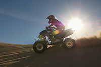 Man riding quad bike in desert against sun