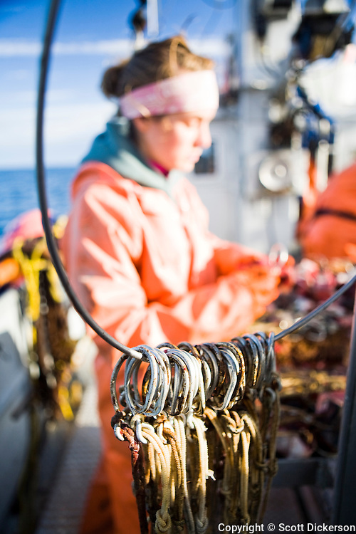Circle hooks used for commercial longline fishing for halibut frame Claire Laukitis as she baits hooks while fishing in the Aleutian Islands, Alaska.