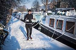 © Licensed to London News Pictures. 28/02/2018. London, UK. A wan takes a jog through picturesque scenes at sunrise in Little Venice, West London following heavy snowfall last night. Large parts of the UK are experiencing disruption as 'Storm Emma' hits, following Russian a cold front earlier in the week named 'The Beast From The East'. Photo credit: Ben Cawthra/LNP