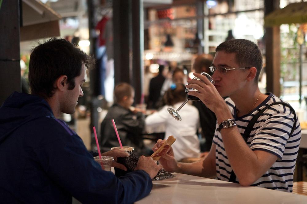 Two young men enjoy tapas at Mercado de San Miguel, in Madrid, Spain.