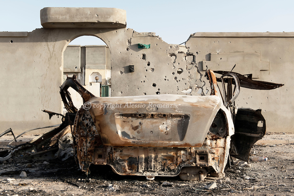 Libya: Riddled by gunshots wall and burned car in 700 neighbourhood in Sirte. Alessio Romenzi