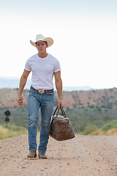 rugged young cowboy carrying a bag and walking on a dirt road