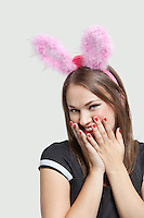 Shy young woman wearing rabbit ears over gray background