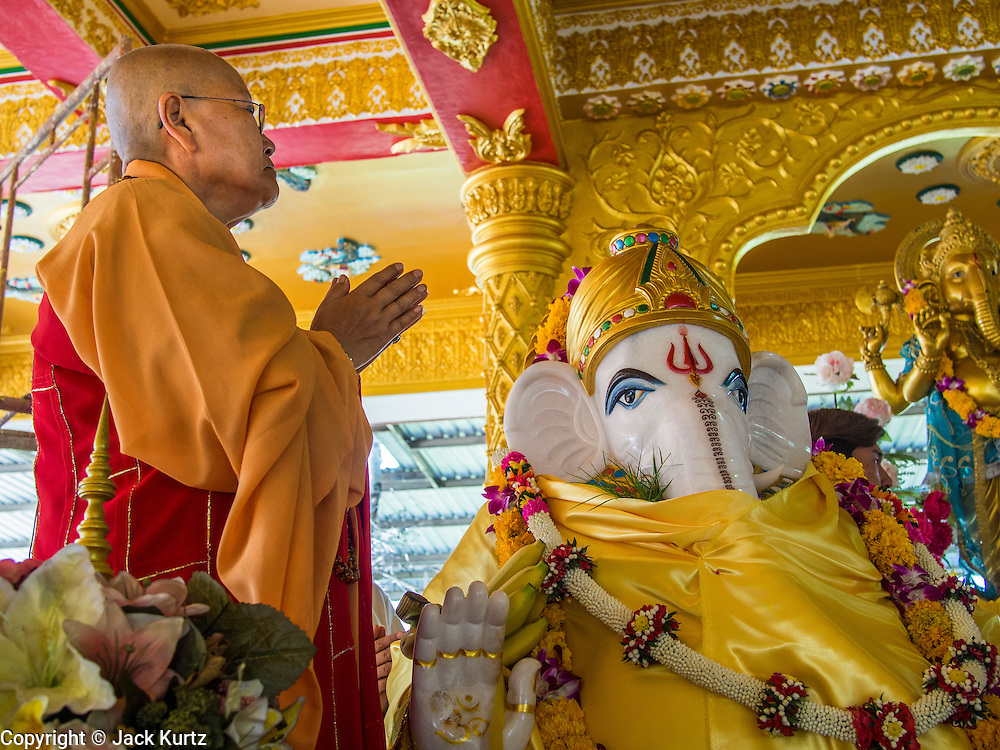 "09 SEPTEMBER 2013 - BANGKOK, THAILAND:  A Buddhist monk blesses a statue of Ganesha at Shiva Temple in Bangkok. Ganesha Chaturthi also known as Vinayaka Chaturthi, is the Hindu festival celebrated on the day of the re-birth of Lord Ganesha, the son of Shiva and Parvati. The festival, also known as Ganeshotsav (""Festival of Ganesha"") is observed in the Hindu calendar month of Bhaadrapada. The date usually falls between 19 August and 20 September. The festival lasts for 10 days, ending on Anant Chaturdashi. Ganesha is a widely worshipped Hindu deity and is revered by many Thai Buddhists. Ganesha is widely revered as the remover of obstacles, the patron of arts and sciences and the deva of intellect and wisdom.    PHOTO BY JACK KURTZ"