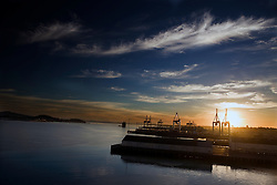 The sun rises over Waitemata Harbour and Auckland's shipping port, Auckland, New Zealand