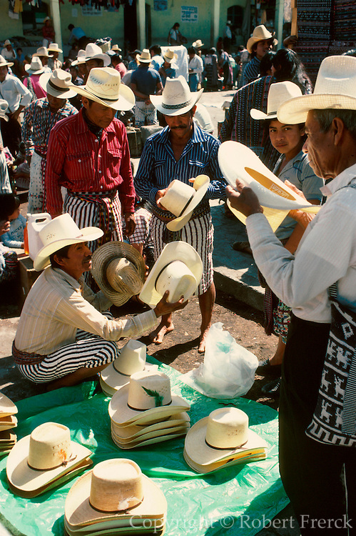 GUATEMALA, HIGHLANDS, MARKETS Market day in the village of Santiago on Lake Atitlan, men buying and selling straw hats