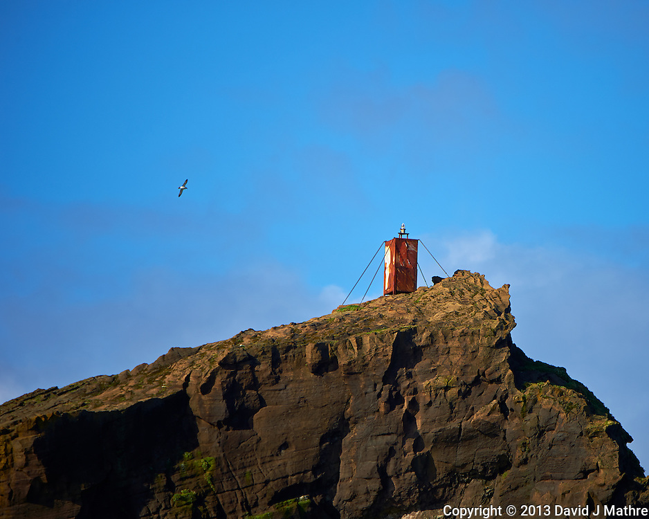 Unmanned Light On Top of Geirfuglasker Island. Geirfuglasker is a small island part of the Vestmannaeyjar archipelago off the southwest coast of Iceland. Historical note last refuge of the Great Auk before they went extinct (http://en.wikipedia.org/wiki/Geirfuglasker). There must be a generator up there, but I don't know how the light is serviced? Image taken with a Nikon D4 and 80-400 mm VRII lens (ISO 140, 400 mm, f/5.6, 1/1000 sec) while traveling on a small zodiac from Heimaey to Surtsey Island. Nikonians Photo Adventure in Iceland.