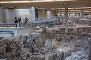Akrotiri, an ancient settlement on Santorini, Greece, dating back to 4500 BC, was covered by volcanic pumice and ash in 1700 BC.  The ruins have been uncovered and are under a protective roof.  Visitors walk on boardwalk across the top of the unearthed settlement.
