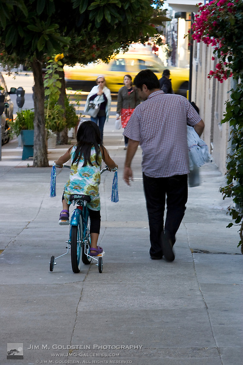A father watches his daughter rider her bike in the Haigh Ashbury district of San Francisco