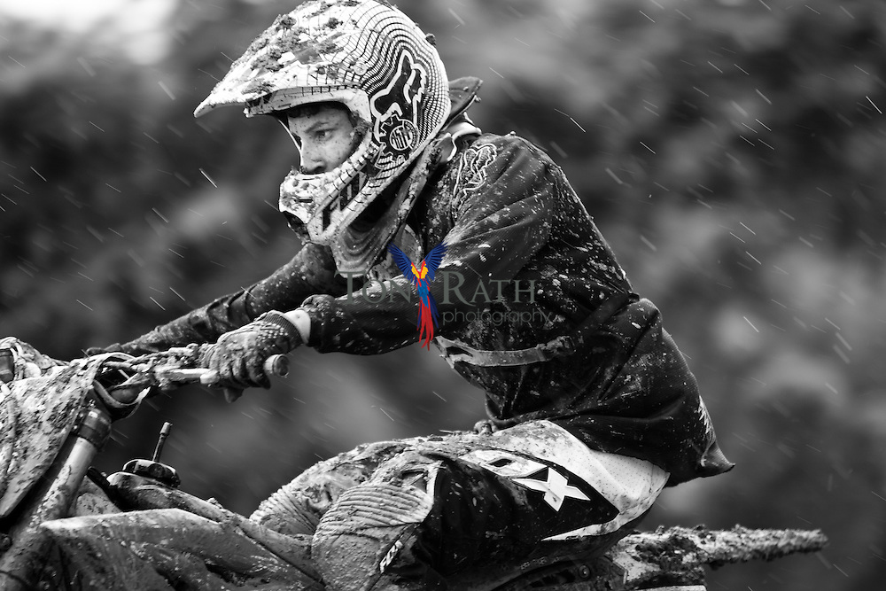 Black and white close-up shows a single male motocross racer splattered with mud in the rain on an outdoor track in Belmopan, Belize.