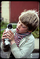 Boy holds rescued puffin chick as he talks to it before taking it to shore to free; Westmann Is Iceland