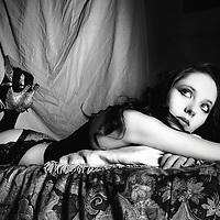 A young woman in suspenders lying on a bed