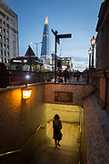 With the Shard in the background, a lady pedestrian descends steps into the tunnel under London Bridge during the evening rush-hour, on 8th November 2018, in London, England.