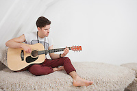Young man playing guitar while sitting on fur sofa