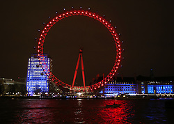 © Licensed to London News Pictures. 01/12/2015. London, UK. London's Coca-Cola London Eye is  lit RED tonight to mark World AIDS Day. Every year, a number of buildings and monuments around the globe are illuminated RED on December 1 to raise awareness around the fight to end AIDS. Photo credit: Peter Macdiarmid/LNP