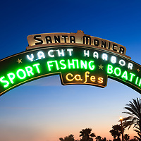"Photo of Santa Monica Pier sign at dusk. The neon sign is on Colorado Avenue at the entrance of the Santa Monica Pier and says ""Santa Monica Yacht Harbor Sport Fishing Boating Cafes"". Santa Monica Pier is a landmark located in Los Angeles County Southern California and has an amusement park with a ferris wheel, roller coaster, restaurants, and other attractions."