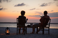 Adult man and adult woman are silhouetted at dusk as they have glass of wine on the beach, Zanzibar archipelago, Tanzania.