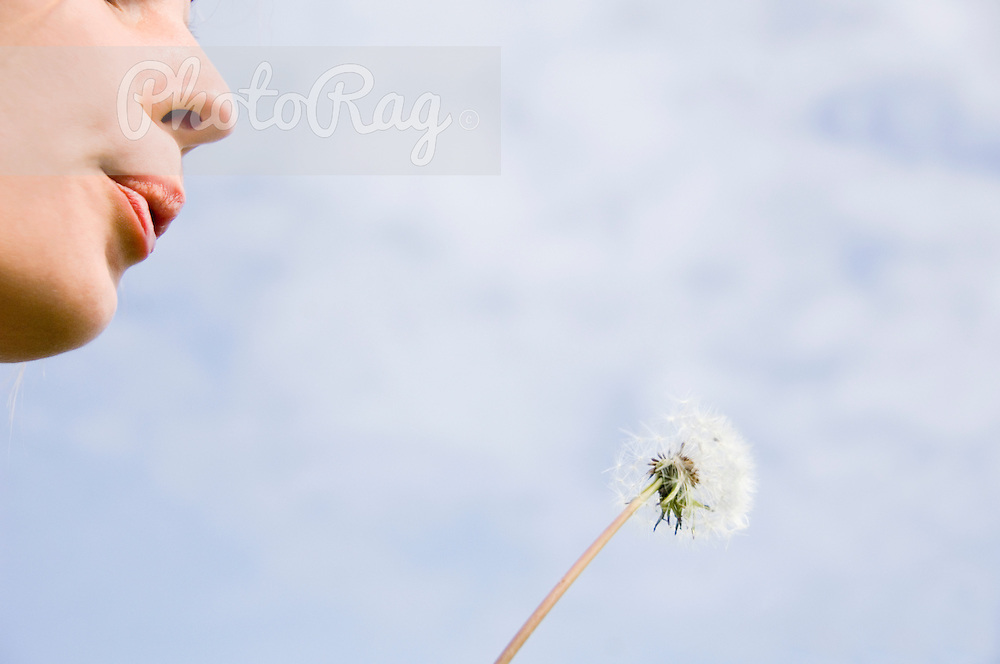 A young woman is blowing a dandilion flower while making a wish on a beach in Donegal, Republic of Ireland.