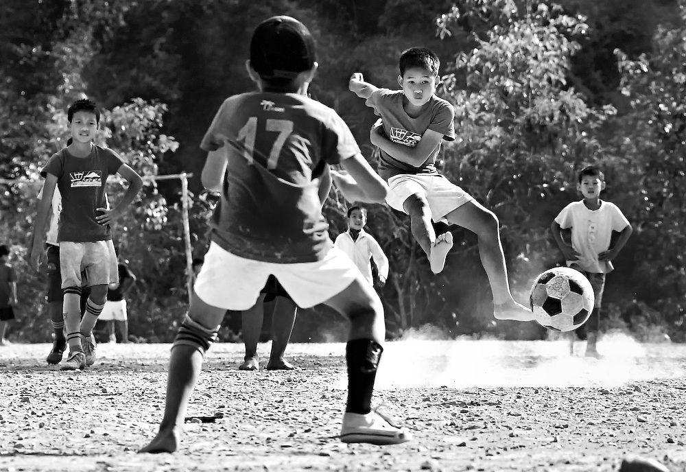 School boys play football on a gravel field in there home village near Luang Prabang, Laos.