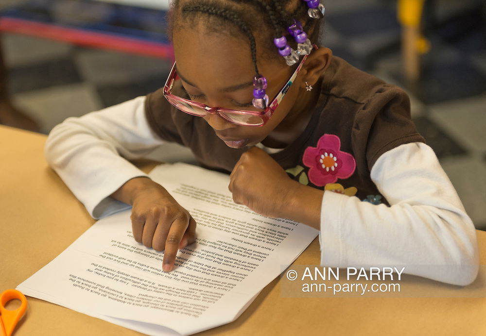 """Garden City, New York, U.S. January 20, 2014. JAEL CHARLTON, 6, of Freeport, reads King's 1963 """"I Have a Dream Speech"""" at the program Dreaming with Dr. Martin Luther King, Jr. where children explored Dr. King's life and then created an artwork of peace, at the Long Island Children's Museum, to celebrate the American official federal holiday Birthday of Martin Luther King, Jr."""