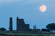 A rising supermoon (perigee full moon) above Magpie Mine, a disused lead mine near Sheldon, Peak District, UK. 10th August 2014.