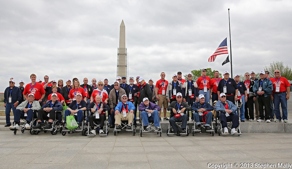 The last of the three busloads of Veterans and guardians pose for a picture during the Sullivan-Hartogh-Davis Post 730 Honor Flight at the National World War II Memorial in Washington, DC on Tuesday, April 16, 2013. About 90 veterans were on the trip. After their visit to the National World War II Memorial they would take a bus tour of Washington, DC followed by a visit to the Korean War Veterans Memorial.