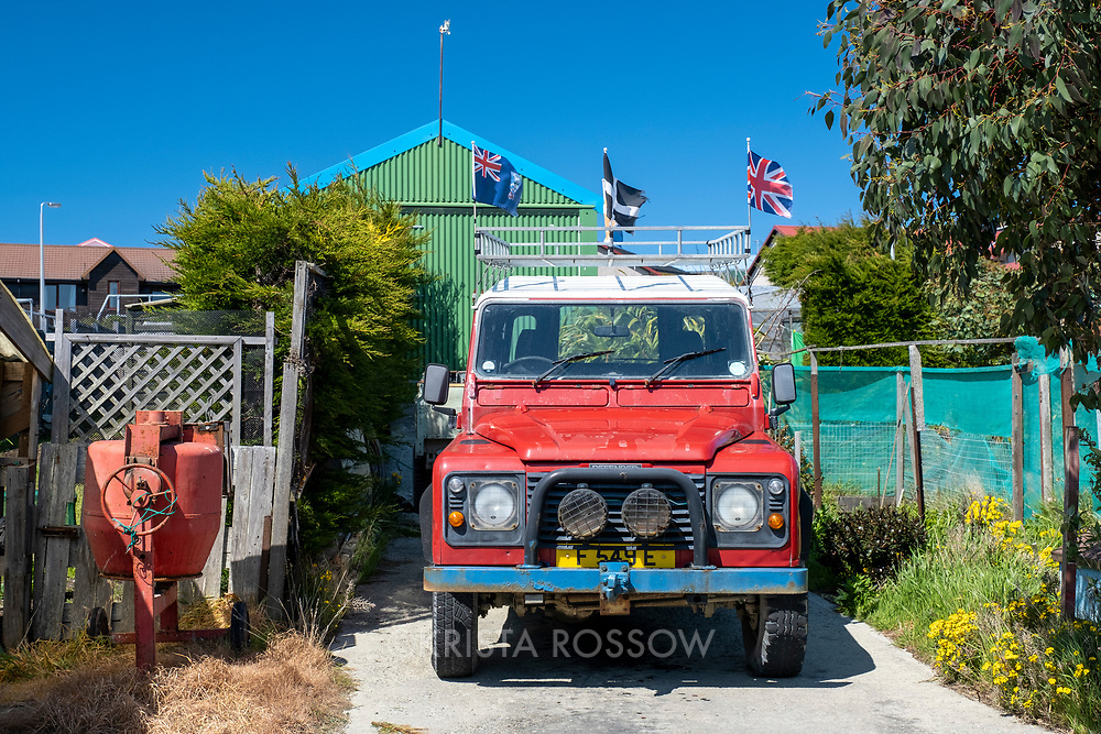 A land rover bearing the British and Falklands flags parked in a driveway in Stanley, East Falkland Island, Falkland Islands.