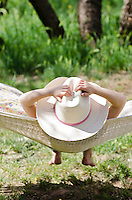 A girl relaxing on a hammock with her  cowgirl hat at Dead Horse State Park, Arizona.