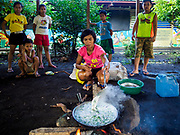 20 JANUARY 2018 - CAMALIG, ALBAY, PHILIPPINES: SONNY SACAYAN cooks green beans with coconut milk at the Barangay Cabangan evacuee shelter in a school in Camalig. She will serve her family some of the food and sell some of it. There are about 650 people living at the shelter. They won't be allowed to move back to their homes until officials determine that Mayon volcano is safe and not likely to erupt. More than 30,000 people have been evacuated from communities on the near the Mayon volcano in Albay province in the Philippines. Most of the evacuees are staying at school in communities outside of the evacuation zone.  PHOTO BY JACK KURTZ