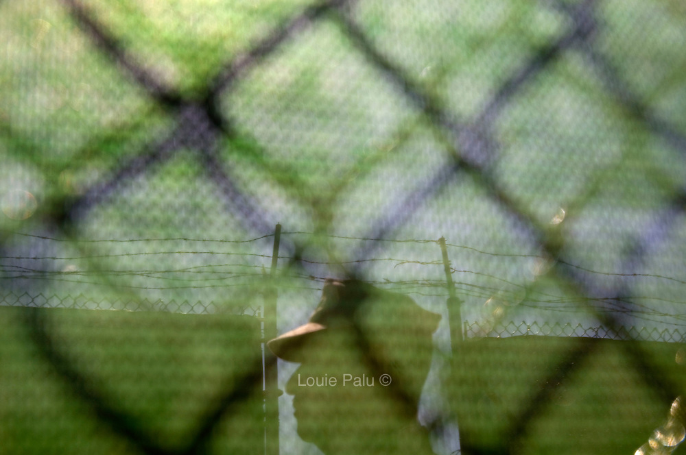 A member of the US military seen from behind a fence in Camp Delta at the Guantanamo Bay Detention Facility located on the US Naval Station in Guantanamo Bay, Cuba. Approximately 240 detainees accused of plotting and assisting in terrorist activities continue to be held in the facility after the attacks on the United States on September 11, 2001, while some are cleared for release. The US administration is working toward a solution as to the future of many of the detainees after US President Barack Obama signed an order to close the detention facility earlier this year.
