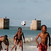 Jongens voetballen op een strand in Zuid Afrika, op de achtergrond een kunstwerk van een voetbalgoal.