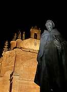 """Low angle view of statue of Padre Vitoria, outside the Convent of St. Stephen, Salamanca, Spain, pictured on December 19, 2010 at night, floodlit. Commissioned by order Juan Alvarez de Toledo, Bishop of Cordoba, and designed by Juan de Alava, the church was built 1525-1618. The main portal, c.1660, has a row of decorated arches and a tympanum with a relief of the """"Martyrdom of St. Stephen"""", by Juan Antonio Ceroni. Above it is a frieze in Italian style, depicting Calvary crowned by the Eternal Father. Salamanca, an important Spanish University city, is known as La Ciudad Dorada (""""The golden city"""") because of the unique golden colour of its Renaissance sandstone buildings. Founded in 1218 its University is still one of the most important in Spain. Around it the Old Town is a UNESCO World Heritage Site. Picture by Manuel Cohen"""