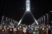 Nederland, Nijmegen, 23-11-2013Zaterdag is de nieuwe stadsbrug van de stad Nijmegen, de Oversteek, in gebruik genomen, geopend. Op de foto neemt het publiek de brug in bezit. Ongeveer 10.000 mensen liepen naar de andere kant en terug. Dit gebeurde door het in twee jeeps afrijden van de brug van Zuid naar Noord door de twee enige nog levende veteranen van de oversteek in 1944. De brug is vernoemd naar de heldhaftige oversteek van de rivier de Waal die Amerikaanse soldaten op dit punt maakten tijdens de operatie Market Garden in de tweede wereldoorlog om met succes de oude Waalbrug te veroveren. De overspanning is een belangrijke schakel in de ontlasting van de stad van het doorgaande verkeerDe Oversteek is een boogbrug van 285 meter lang en 60 meter hoog en is de op een na langste hoofd overspanning van Nederland, en de grootste boogbrug van Europa met een enkelvoudige boog.De brug wordt 23 november in gebruik genomen.De nieuwe oeververbinding moet zorgen voor een betere spreiding en doorstroming van verkeer binnen de stad Nijmegen. Na 75 jaar is er eindelijk een tweede vaste verbinding voor de stad. De oude waalbrug krijgt vanaf eind dit jaar groot onderhoud, waarna de volle capaciteit van beide bruggen pas gebruikt kan worden. De skyline van de stad is veranderd.De brug is een ontwerp van de Belgische architecten Ney en Paulissen. Foto: Flip Franssen