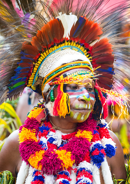 Portrait of a woman dancing and wearing traditional tribal dress for the Goroka Show, an annual Singsing Festival in the highlands of Papua New Guinea. She is wearing colourful necklaces of flowers and a large headdress adorned with birds feathers.