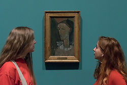 """© Licensed to London News Pictures. 21/11/2017. London, UK.  Staff members view """"Self Portrait as Pierrot"""", 1915.  Preview of """"Modigliani"""", the most comprehensive exhibition of works by Amedeo Modigliani ever held in the UK.  On display are iconic portraits, sculptures and 12 nudes, the largest group ever shown in the UK.  The show runs 23 November to 2 April 2018.  Photo credit: Stephen Chung/LNP"""