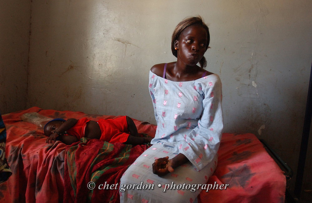 DIOSSONG, SENEGAL.  Senegalese mother sits with her child infected with malaria in the Medical Center of Diossong, Senegal on Tuesday, October 31, 2006.    © Chet Gordon/ THE IMAGE WORKS