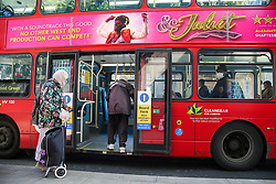 © Licensed to London News Pictures. 20/04/2020. London, UK. Passengers use the middle-door for boarding a London bus. Transport for London has introduced middle-door boarding during the coronavirus outbreak and to slow the spread of COVID-19. The passengers are no longer able to pay their fare using the Oyster/contactless card reader which are next to the driver's seat. Photo credit: Dinendra Haria/LNP