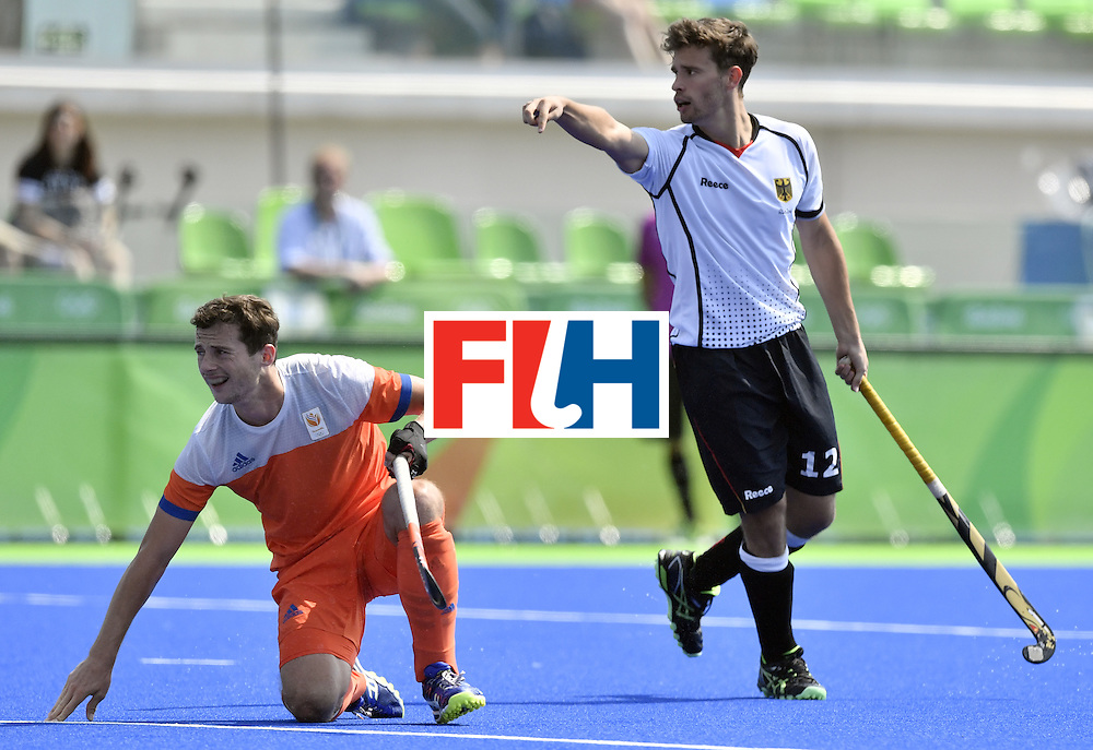 Germany's Timm Herzbruch (R) gestures beside Netherlands' Sander Baart during the men's Bronze medal field hockey Netherlands vs Germany match of the Rio 2016 Olympics Games at the Olympic Hockey Centre in Rio de Janeiro on August 18, 2016. / AFP / PHILIPPE LOPEZ        (Photo credit should read PHILIPPE LOPEZ/AFP/Getty Images)