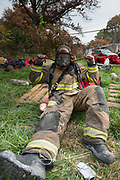A firefighter puts on fire fighting equipment in a grassy field.