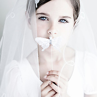 Female youth wearing white veil holding silver butterfly looking at camera