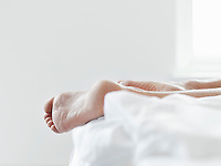 Young woman lying on bed close-up of feet