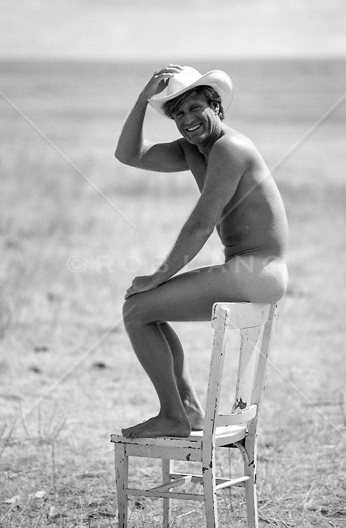 naked cowboy sitting on the back of a chair outdoors on a ranch
