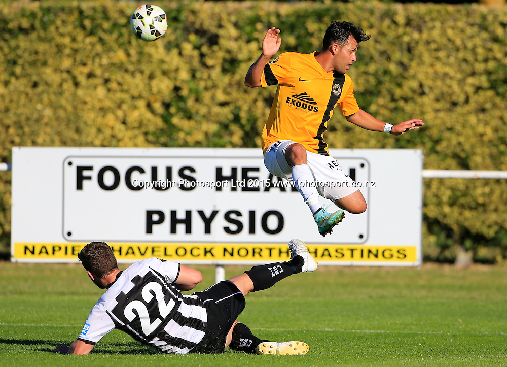 Wellington's Luis Corrales jumps over a tackle by Billy Scott. Hawkes Bay United v Wellinton, Semi final leg 1, ASB Premiership football, Park Island, Napier, New Zealand. Saturday, 21 March, 2015. Copyright photo: John Cowpland / www.photosport.co.nz