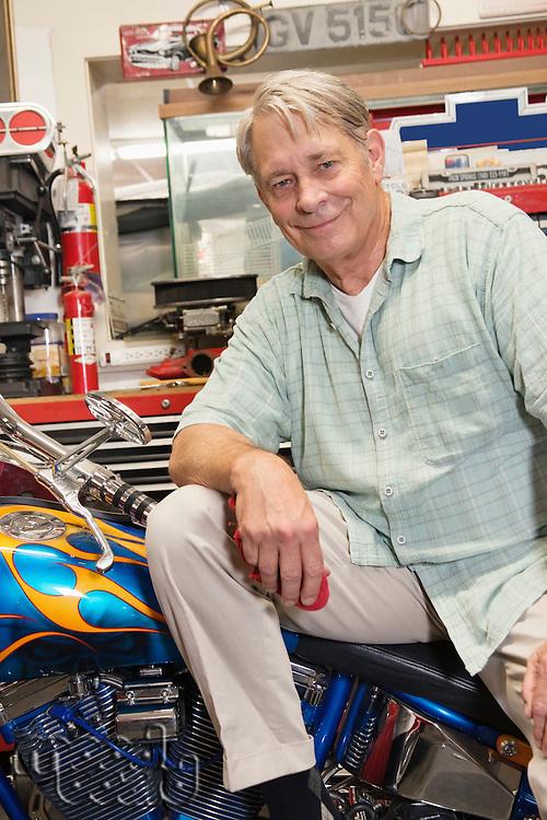 Portrait of senior man sitting on motorcycle in workshop